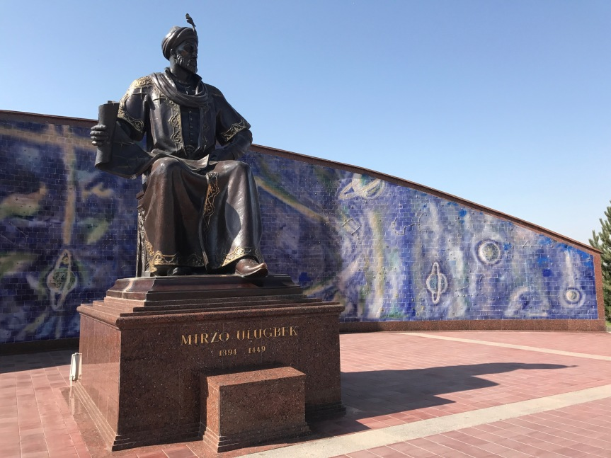 A statue of Ulugh Beg with an astronomical mural located behind him